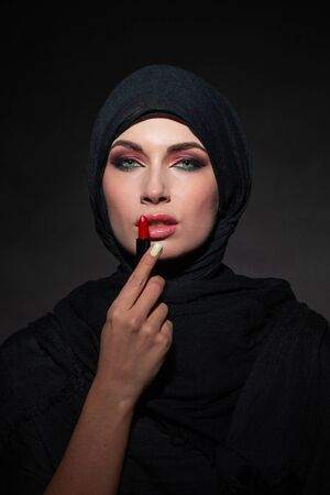 Portrait of an arab saudi emirates woman painting her lips with a lipstick on black background