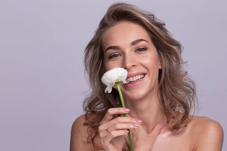 Portrait of beautiful blonde woman with white rose 写真素材