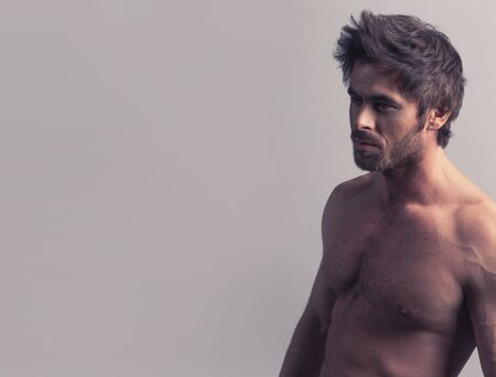 Dark shot of healthy muscular naked young man on gray background 写真素材
