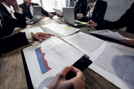 Group of diverse business executives holding a meeting around a table discussing graphs charts showing statistical data analysis