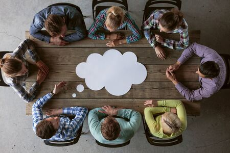 Hipster business teamwork brainstorming planning meeting concept, people sitting around the table with white paper shaped like dialog cloud Stockfoto