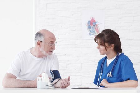 Doctor measuring blood pressure of male senior patient 写真素材