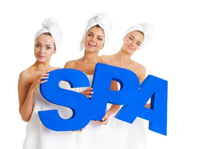 Women wrapped in towels holding SPA letters isolated on white background 写真素材