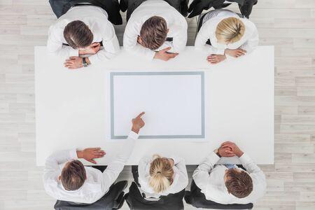 Business, people and team work concept - close up of creative team sitting at table and pointing finger to blank copy space for text