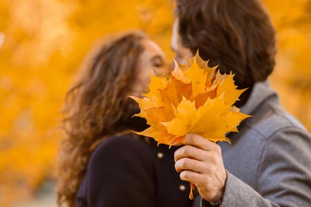 love, relationship, family and people concept - couple with maple leaves kissing in autumn park