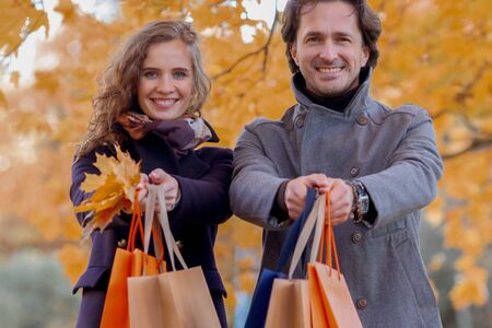 Couple with shopping paper bags in fall forest , autumn sale concept