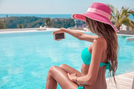 Portrait of a beautiful woman in bikini and sunhat making selfie photo on smartphone outdoors sitting at tourist resort by the pool
