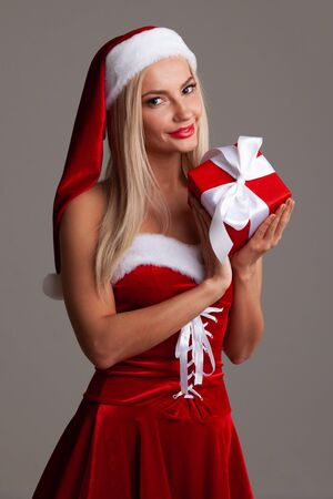 Happy excited young woman in santa dress and hat with gift box on gray background 写真素材