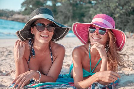 Beautiful young women in sunhats laying on beach 写真素材