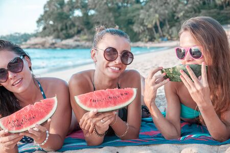 Happy smiling female friends eating watermelon on beach