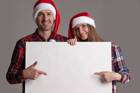Happy couple in Santa hats holding blank banner and pointing at copy space