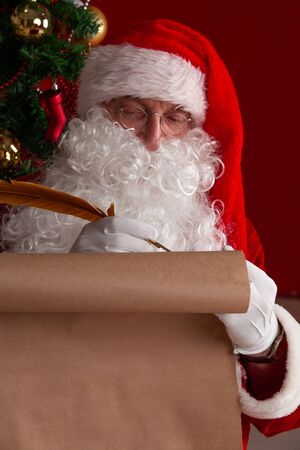 Santa Claus sitting at home and writing on old paper roll to do list with quill pen and ink 写真素材