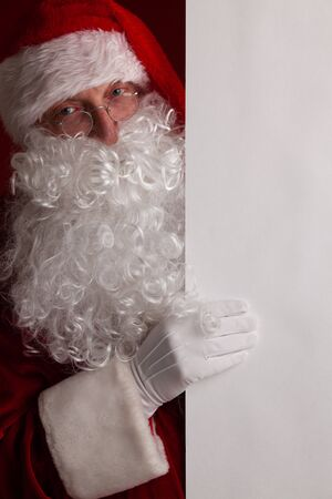 Santa Claus holding white paper billboard with copy space for text