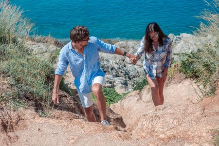 Man and woman tourists walking hand in hand exploring coastline in the mountains by the sea