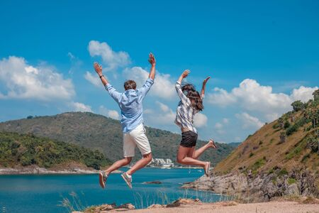 Young couple jumping, beautiful sea view on background 写真素材