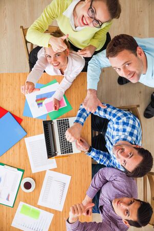 Business team meeting, people in casual clothes working with financial statistics at office desk showing thumbs up