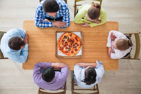 People hands grabbing pizza from delivery box, top view