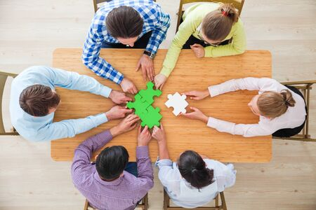 Hipster business successful teamwork concept, business people group assembling jigsaw puzzle, top view