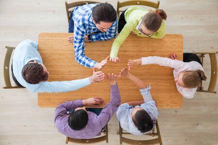 Współpracownicy przybijają piątkę siedząc przy biurku, widok z góry top
