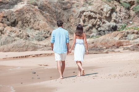 Happy couple walking on sand of tropical beach