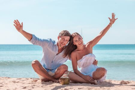 Happy smiling couple sitting on beach with raised arms