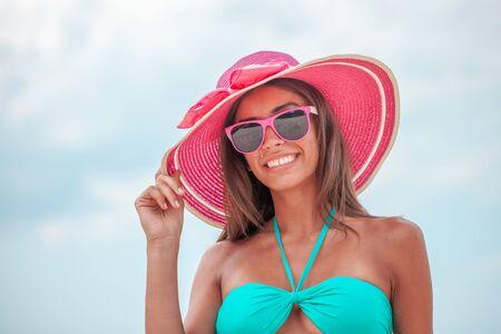 Portrait of a beautiful smiling young woman in bikini and sunhat