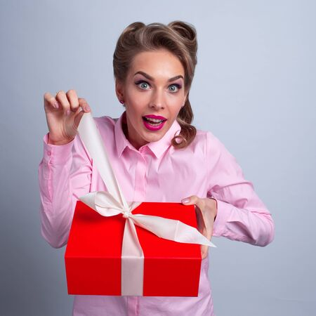 Hmm what is it! Funny woman pulling ribbon of bow on gift box and want to open. Christmas, new year, birthday, Valentine, Valentines day