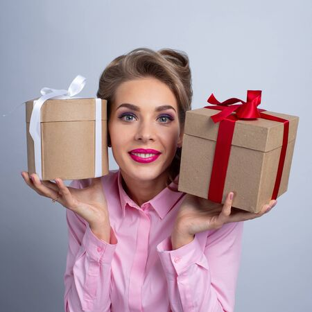 Young happy woman puts her ear to holiday presents with bows