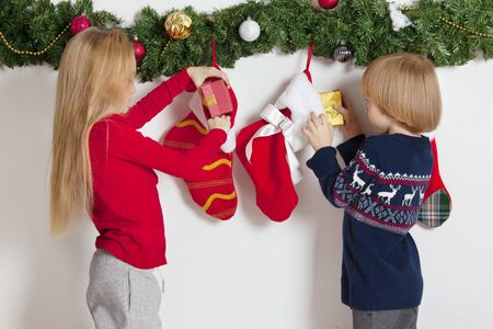 Adorable little children open their stocking gifts on Christmas morning