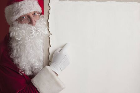 Santa Claus holding vintage paper billboard with copy space for text