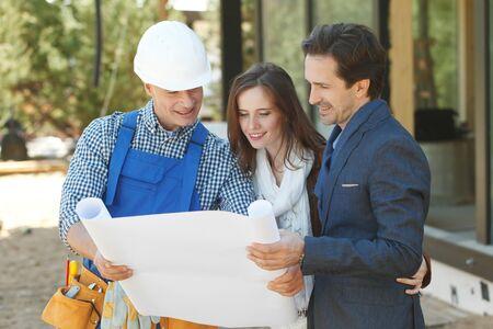 Capataz muestra los planes de diseño de la casa a una joven pareja en el sitio de construcción al aire libre