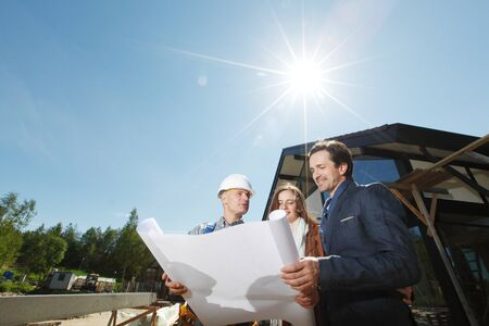 Foreman shows house design plans to a young couple at construction site outdoors at sunny day