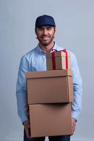 Happy smiling delivery man in uniform cap holding box stack 写真素材