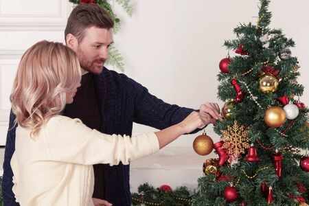 Young couple decorating Christmas tree putting on xmas balls together