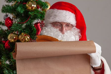Santa Claus sitting near Christmas tree and writing on old paper roll to do list nice or naughty with quill pen and ink
