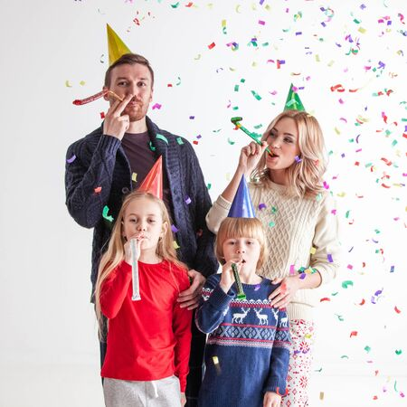 Family blowing party trumpets with confetti celebrating new year, gray background with copy space for text