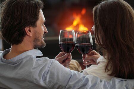 Romantisches Paar, das Wein zu Hause nahe Kamin trinkt