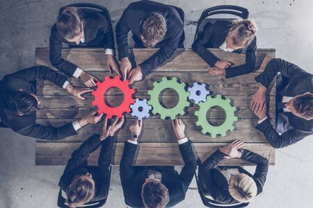 Business people joining gears on table at workplace problem solution strategy teamwork concet