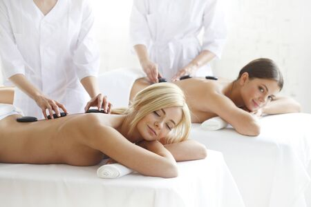 Pretty friends getting hot stone massage together in the health spa Stock Photo