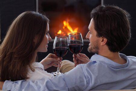 Nahaufnahme eines jungen Paares, das Wein vor einem offenen Holzfeuer am Valentinstag trinkt