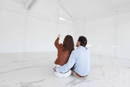 Happy couple at big bright comfort apartment planning their future