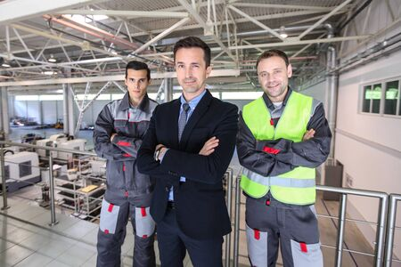 Portrait of business man and workers at factory teamwork cooperation concept Stockfoto