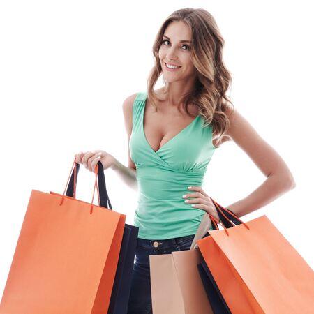 Mujer de compras feliz sonriendo sosteniendo bolsas de la compra aislado sobre fondo blanco. Foto de archivo