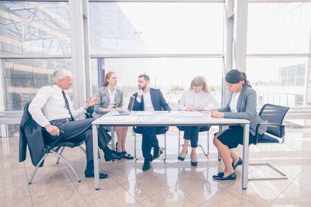 Geschäftsteam sitzt am Tisch und arbeitet mit Laptop und Dokumenten im Büro