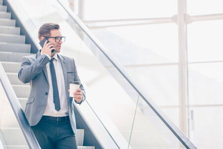 Businessman on escalator talking on phone and holding coffee in hand