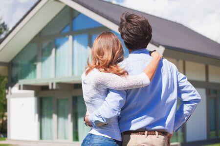 Un couple heureux se tient à l'extérieur dans ses bras et regarde sa nouvelle maison