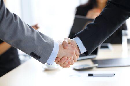 Biznesowy uścisk dłoni w biurze, zespół roboczy w tle