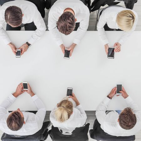 Business people using smartphones sitting at table in office, white copy space background