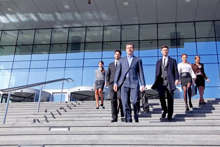 Group of business people and their leader walking down stairs outside office building successul deal negotiation concept Foto de archivo