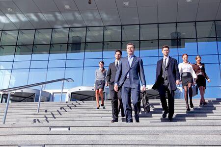 Groupe d'hommes d'affaires et leur chef descendant les escaliers à l'extérieur du concept de négociation d'un accord réussi d'un immeuble de bureaux Banque d'images